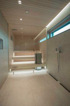 Kaunis. Vaaleanraikkaat ja kuitenkin lämpimänsävyiset pinnat, harmoninen lämminsävyinen valaistus ja vaalea sauna. Pelkkä lasi saunana ja kylpytilan välissä hyvä! Tässä myös tosi kauniisti sopii että saunan puupaneelikatto jatkuu kylpyhuoneen puolelle.