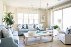 Lovely blue and white living room features a CFC Gimso Coffee Table seating two powder blue couches topped with white and blue pillows and two off white accent chairs placed on either side of a round white pedestal accent table.