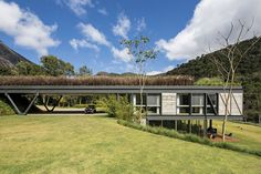 JG House by MPGARQUITETURA, the intention was to create a huge garden on top, in order to make the construction disappear on the landscape and make it work as a visual bridge connecting to the slopes of the valley that splits the land of 350.000 square meters