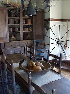 Prim dining room with wood cabinet, dough bowl, table, ladder back chairs, chandelier and spinning wheel - very nice!