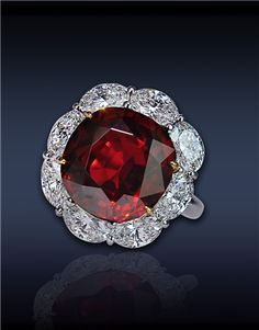 Ruby & Diamond Solitaire:   10.01 Ct Cushion Cut Ruby, Surrounded by 3.74 Ct Oval Cut Diamonds (8 Stones), Mounted in Platinum and 18K Yellow Gold.