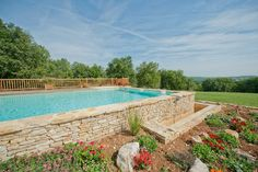 Swimming Pools Built on Slopes | Above ground swimming pool on sloping ground with stone wall to match ...