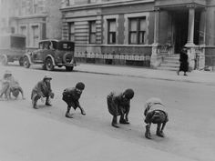 Children playing a game of leapfrog in a street in Harlem New York