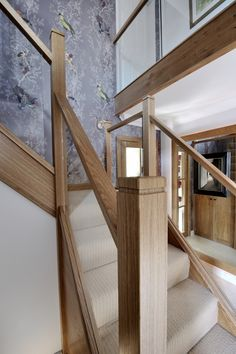 A centrally-positioned mixed modern glass and natural oak staircase with a half-landing turn and gallery landing. Light coloured carpet, wooden feature step and beautiful purple patterned wallpaper. Carpet Staircase, House Staircase, Staircase Remodel, Staircase Ideas, Timber Stair, Modern Stair Railing, Modern Stairs, Glass Stairs Design, Glass Stair Balustrade