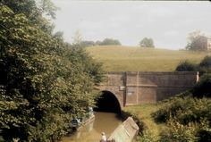 BW197-2-26-36 a portal of Crick Tunnel with a British Waterways flat workboat moored on the offside Date August 1974