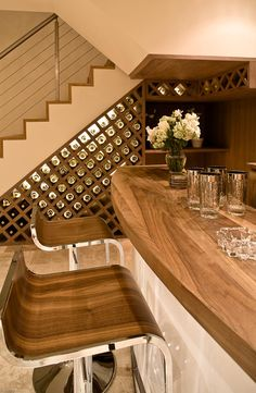"""Daun Curry really knows how to make wine shine. The lighting shining from behind the bottles creates a subtle, warm glow. Notice how the storage travels across the adjacent wall to continue the design and highlight the wine as a central piece of art. Who wouldn't want to lounge at this home bar with family and friends?!"" #wine #storage"