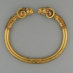 A mid 19th Century Italian Etruscan gold hinged bangle. With twin Ram's Head terminals.