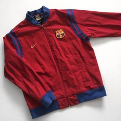 """FC Barcelona Nike Bomber Jacket Vintage Rare CFB Like new, gently worn. Vintage inspired FC Barcelona Jacket From Nike Futbol Classics """"Inspired by Football's Glorious Past"""". Cool unique bomber jacket style in team colors. Extremely rare. Has 1940s FC Barcelona Crest """"CFB"""" and Nike Swoosh. Modern FC Barcelona Crest on inside of jacket. Crest has some fraying, was like that originally. Great vintage look with worn-in/faded edges. Red outside is denim.  Measurements around: 27.5""""in sleeve…"""