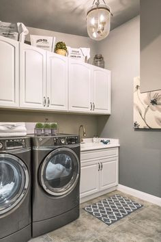 Simple laundry room with white cabinets, grey washer/dryer, and rustic lighting | Room Resolutions