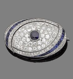 A sapphire and diamond brooch, circa 1915.  The pierced oval brooch set to the centre with a circular mixed-cut sapphire, surrounded by old brilliant-cut diamonds, within an asymmetrical border of single-cut diamonds and calibré-cut sapphires, diamonds approx. 2.50cts total, length 4.0cm, fitted case by Cartier