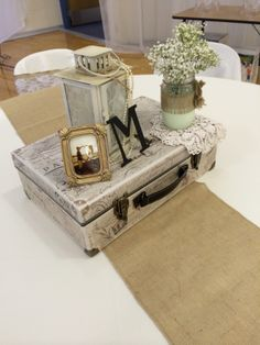 Vintage centerpiece using a suitcase, lantern with pearls, jars dipped in paint with baby's breath, and a picture of the couple.