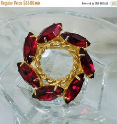 This #vintage garnet red rhinestone Christmas wreath brooch is gorgeous!  It features a gold tone wreath shaped brooch with a braided gold center surrounded by dark garnet r... #ecochic #etsy #jewelry #jewellery