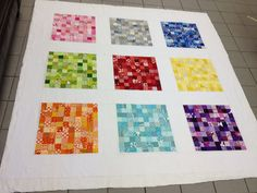 Quilt top basted. Pixelated quilt using a rainbow charm pack. Inspiration for Quilt as you go