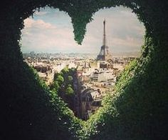 View of Paris through a heart in the hedges