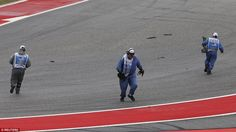 Track workers quickly pick up parts as they clean the track after the collision at the Circuit of The Americas