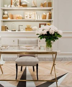 A chic workspace at J.Crew - Beautiful organized bookcase and modern glass desk completed by fresh flowers