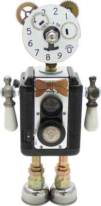 "Name: Zen Zen  D.O.B.: 8/07/10  Height: 12""  Principal Components: Phone dial plate, pressure gauge, camera, faucet handles, hydraulic fittings, wristwatch date rings, clock gears, antique button"