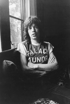 Mick Jagger wears a graphic baseball-style t-shirt with jeans