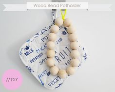 I went to the craft store and bought 15 Wood beads (diameter 30mm / about 1,2 inch) and a stretch chord. You put all 15 beads on the stretch chord and make a double loop on the end. I pulled the chord a bit so my circle would be tight enough. Then I hid the two ends in the last two beads so they weren't visible and voila, done. A quick and simple DIY project to make a nice new design object for your dining table.