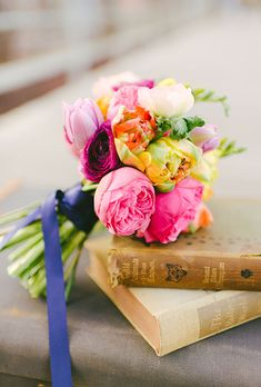 A bright pink-and-yellow posy of peonies and ranuculus by @wildfolkstudio | Brides.com