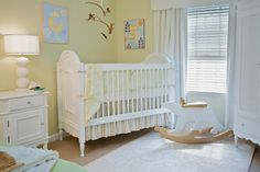 White and yellow nursery features yellow walls as well as tree branch mobile over traditional white crib dressed in Annette Tatum Crib Bedding Set, white and yellow crib bedding and striped crib skirt, next to white French changing table topped with white ripped triple gourd lamp.