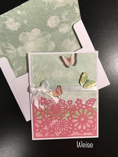 """Butterfly card - 5""""x6.5"""" white card base. Use Hot pink cutout design from Recollections 5x7 paper stack. Cut pink paper in   half and snip around flowers on top half.  Background designer paper is from DCWV Butterfly Garden Stack. Adhere pink cutout paper to background paper. Cut out two additional butterflies from leftover scraps and adhere just the body; fold up wings for 3D effect. Stamp and emboss sentiment in white. Created by: Melanie Weise"""