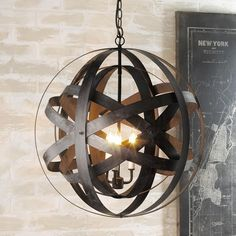 """Double Metal Strap Globe Lantern Two metal strap globes nest inside one another in this modern industrial inspired lantern. Oxidized iron finished straps can be adjusted individually to your desired design. Illuminated within from a 3 light cluster, the sphere glows with sleek """"salvage"""" appeal."""