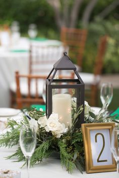 Green, white, and gold color scheme for a winter wedding. White and blush roses, with red berries and pine sprigs. White and green linens with lanterns for the center pieces.