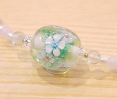 透明色と緑色の二色地に銀箔を細かく散らし、お花を6つ咲かせたとんぼ玉と、水晶、プレナイト、ローズクォーツ、淡水パールを組み合わせてネックレスに仕上げました。金属部分は金色です。サイズとんぼ玉 20mm×19mm全長 42cm(アジャスター+5cm)素材ガラス、水晶、プレナイトローズクォーツ、淡水パール金属部分 メッキギフトラッピングは無料で承ります。尚、プレゼントご希望の方で、贈り先様への直送を希望される場合、 「届け先」にプレゼントの送り先を、「備考」に注文者さま情報を記載いただきますようお願いいたします。また、配達日時指定をご希望の場合は配送方法はゆうパックをご選択ください。定形外郵便やレターパックはあくまでも送り先に受け取り可能な方が常時ご在宅の場合にお使いいただければ幸いです。