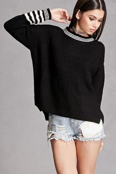 A ribbed knit sweater featuring a striped trim, round neckline, long dropped sleeves, side slits, and a boxy silhouette. This is an independent brand and not a Forever 21 branded item.