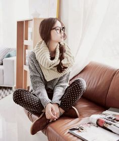 A very comfy outfit with a large oversized scarf, leggings, a warm sweater, and glasses.