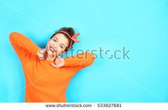 Portrait of expressive young model in orange sweater on blue background
