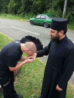 An amazing photo! A guy is kissing humbly the hand of an Eastern Orthodox priest. That's a proof that looks don't matter at all, our soul does :)