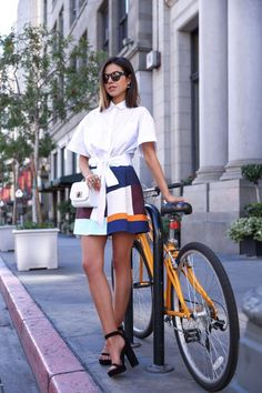 Browse these blogger-approved ways to pose with a bicycle at @Stylecaster | 'Viva Luxury Blog' in white tie-front blouse, colorblock skirt