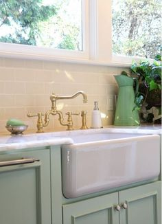 Farmhouse sink is charming and retro w/ pale blue painted cabinets