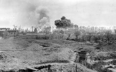 A series of trenches, structures on fire, in a French war zone during World War I.