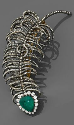 An emerald, diamond, silver and gold brooch, circa 1890.