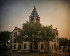 Erath County Courthouse by Joan Carroll. The Erath County Courthouse is a substantial three story edifice constructed of local white limestone and red Pecos sandstone. The tower of the building extends to a height of 95 feet, and the building's base measures 60 by 80 feet. This building presents a variation on a traditional theme in early Texas courthouses of intersecting halls on the first floor