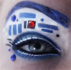 Use a creamy blue liner (or any color you like) to completely shade your lids and brows. Make a series of thick geometric lines and use a metallic liquid liner all along your top lid. With tweezers and lash glue, carefully apply rhinestones.