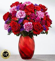 The perfect expression of love and sweet affection, this Valentine's Day bouquet is ready to send your heart's every wish straight to your recipient's door with blooming beauty. Rich red roses are surrounded by a collection of ruffled blooms including hot pink carnations, red mini carnations, purple statice and fuchsia mini carnations, perfectly accented with lush greens. Presented in a stunning red modern glass keepsake vase, this gorgeous bouquet is ready, set, and styled to celebrate love…
