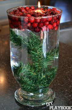 Cranberry Christmas Centerpiece. This is seriously so easy. Take fresh cranberries, a floating candle, and some greenery and add it to a vase with water.