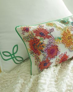 """Inspired by a vintage tablecloth we found at the Brimfield Antiques Show, these #summer blossoms are constructed of hundreds of meticulously stitched French knots atop a printed pattern, for #flowers that burst like fireworks across a white cotton ground and accented with Julep piping. 12"""" x 24"""". Color: Multi  #colorfulliving #accentpillow"""