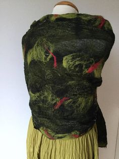This nuno felted collage shawl uses copius quantities of silk pieces layered and pieced together in two layers sandwiching a fine layer of merino wool fibre. On one side black is the dominant shade and on the other green is dominant. The multiple patterns come together to create a