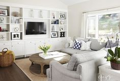 Living room features a dove grey sectional with rolled arms and a wall of white built-in cabinets fitted with open shelves
