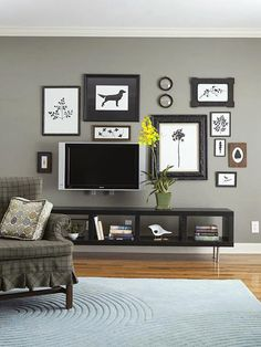 Create a gallery wall including the TV. This one works really well because all the frames and artwork are black and white which relate to the TV.  The gray walls provide less contrast with the black and gives a cohesive look.