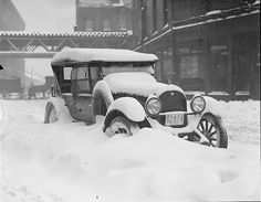 1920 Snow bound car in Boston - notice horse and cart moving in the background.