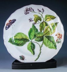 A Chelsea Hans Sloane botanical soup plate c.1755, with painted red anchor mark and shaped brown line rim, boldly painted with a white rose, a small wallflower stem, butterfly and a beetle #ukauctioneers