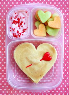 Breakfast For Lunch: Valentine's Day Lunch Box Idea  For the kiddo who prefers breakfast over lunch, prepare a sweet meal they won't be able to resist. Heart-shaped pancakes, heart-shaped fruit, and strawberry yogurt make for a delicious breakfast-for-lunch lunch box idea!