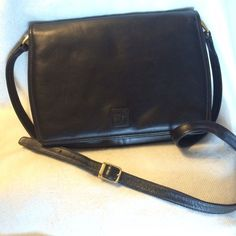 """Anne Klein Black Leather Purse Anne Klein for Calderon black leather purse.  Lion logo on front.  Gently used; some marks on leather in back (see photo) but otherwise clean.  Magnetic closure. Two zippered pouches inside. 8"""" X 11"""" X 2.5""""; could find a small tablet  Strap 40"""" and adjustable.  Great basic!!! Anne Klein Bags Crossbody Bags"""