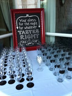 Glasses with chalkboard paint labels so guests can label them whenever they want throughout the night. Wine glass with chalks in the middle on the signing table